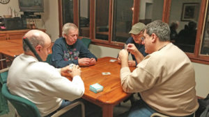 Four men playing cards at a table in their sleeping cabin