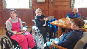 Four MSFL skiers relaxing, 2 in wheelchairs, relaxing around table with hot chocolate