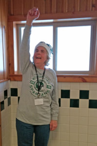 Cheryl Wade with a MSU sweatshirt and hat, raising her arm cheering for Michigan State team