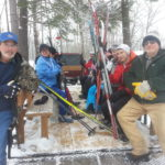 Lions club volunteers in front of wagon loaded with skiers and ski's, headed for the trials