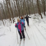 Three cross country skiers, one sight impaired, skiing on groomed trails in the woods