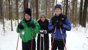 three smiling cross country skiers, one visually impaired