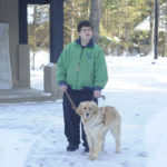 Visually impaired skier and his golden retriever guide dog, outside in the winter at the RAM center