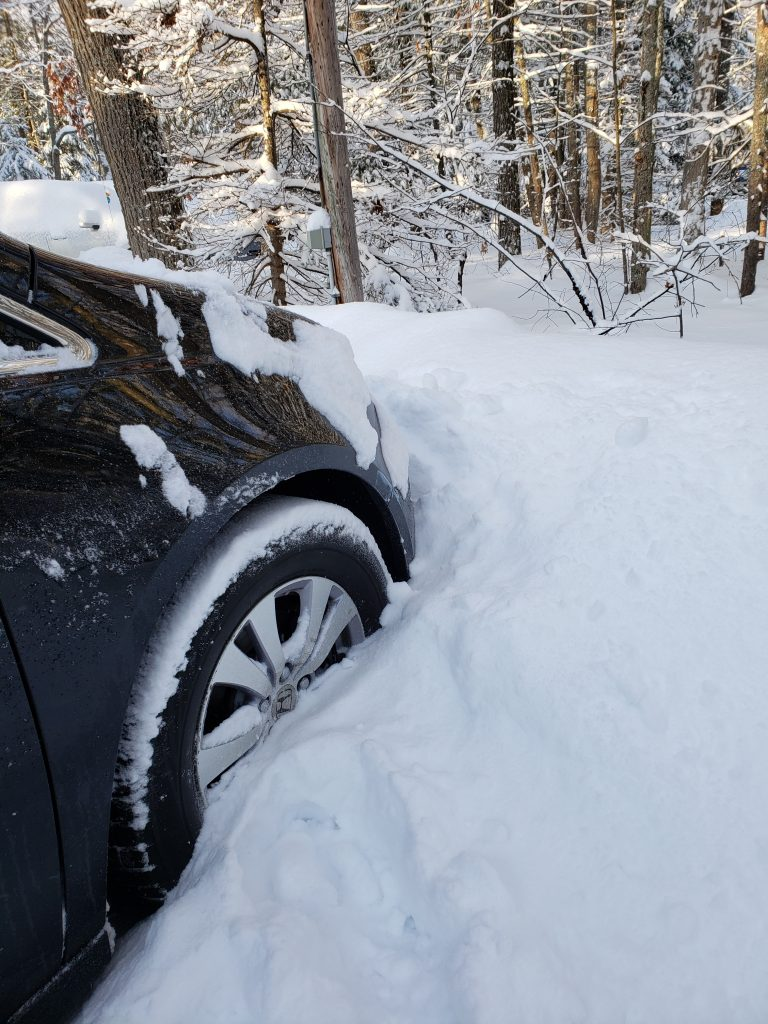 Snow drifting two feet over front tire of car