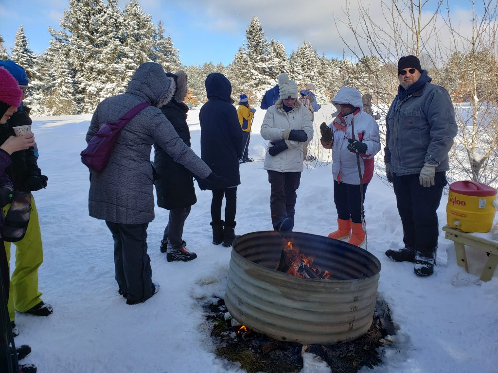 Skiers and volunteers drinking hot chocolate around a fire