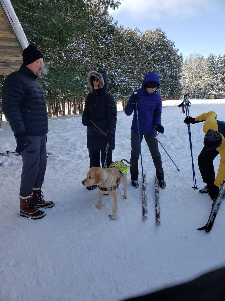 Skier, taking off his ski's, volunteer with guidide og, and another volunteer at the start of the nursery trail