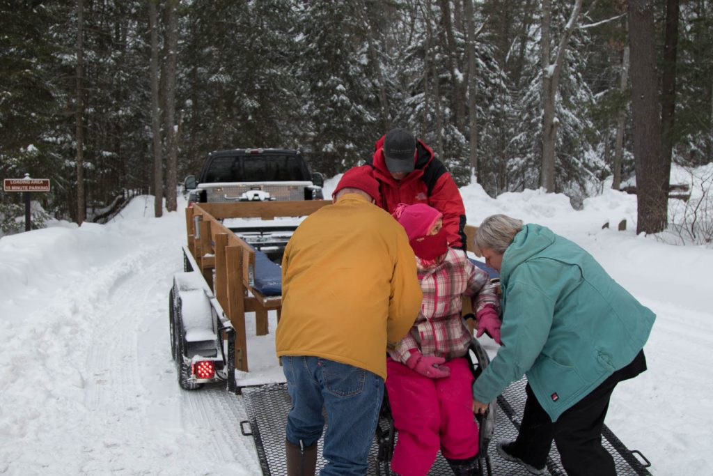 Volunteers loading wheelchair bound person on wagon