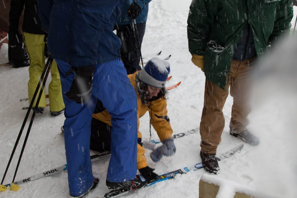Guide helping a skier connect his boots to his ski's