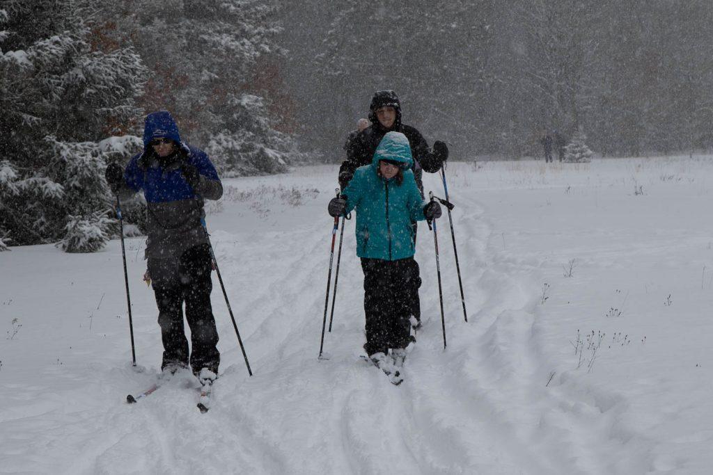 Snowflakes around skiers on the nursery trail