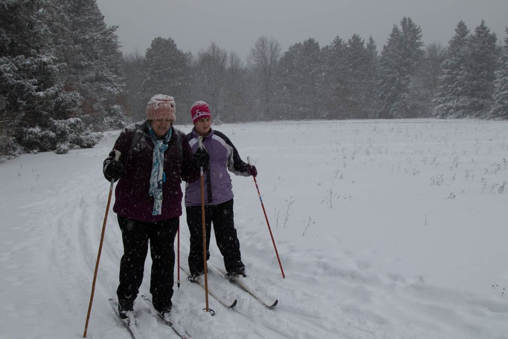 Josie and friend ski in the falling snow