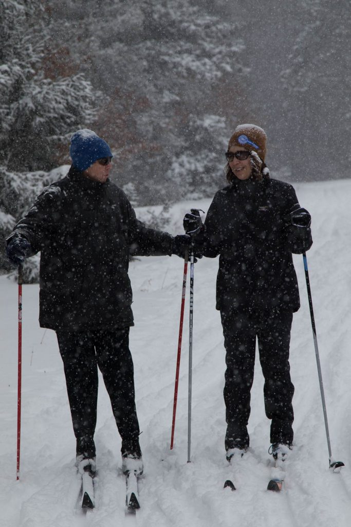 Skier and guide exchange a laugh as they ski with hard snow coming down