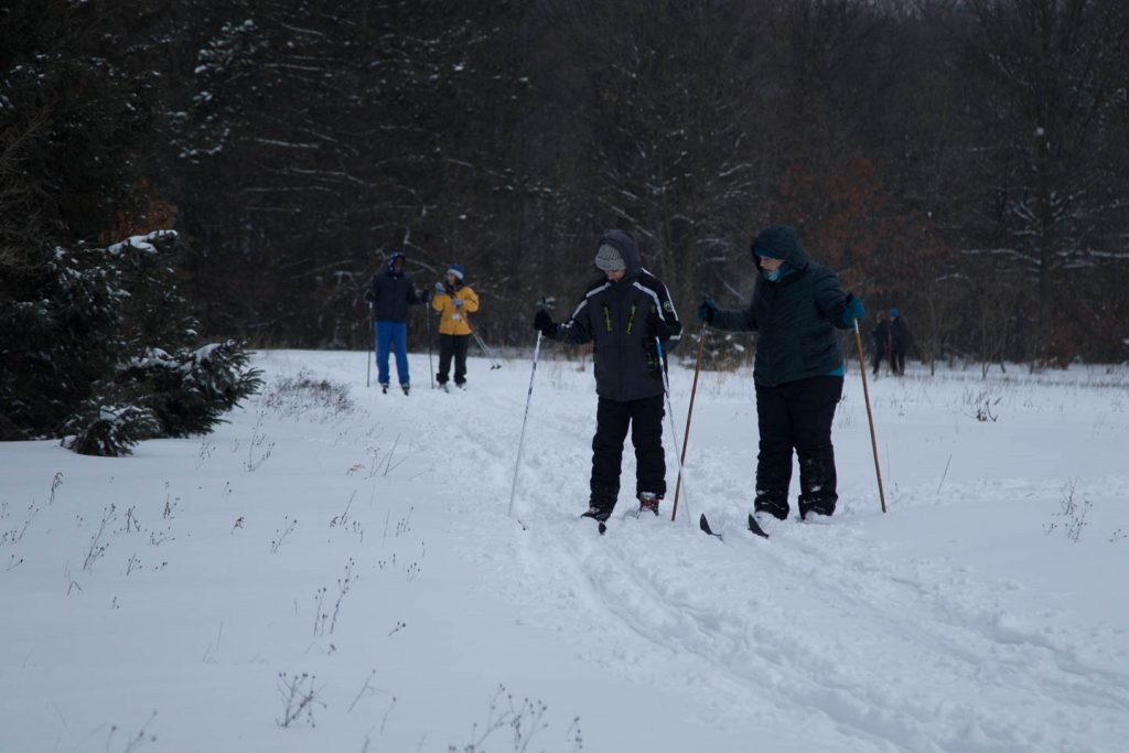 Guide instructs cross country skier how to get back on the groomed trail