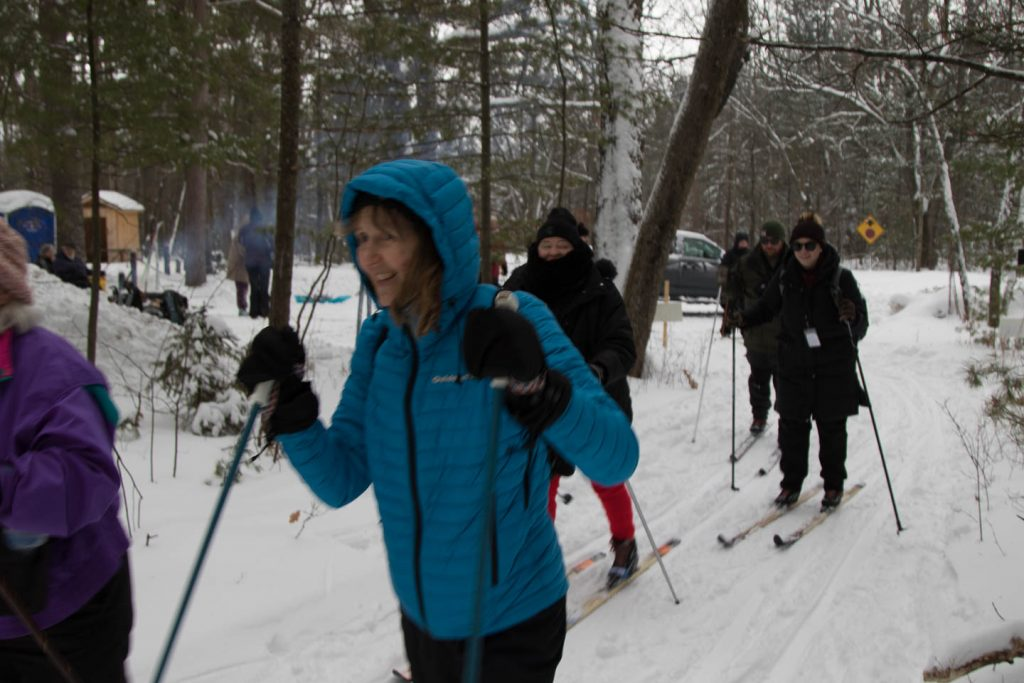 Several cross country skiers start out to ski the trail